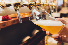 Close-up Of Barman Hand At Beer Tap Pouring A Draught Lager Beer.