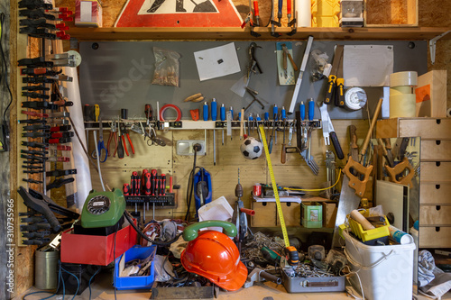 Mess and tools in disorder in a workroom. Equipment, home, interior, rope, dirty, house, messy, objects, stuff, box, chaos, clutter, cluttered #310735966