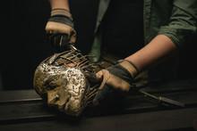 Crop Man Holding Ornamental Metal Skull