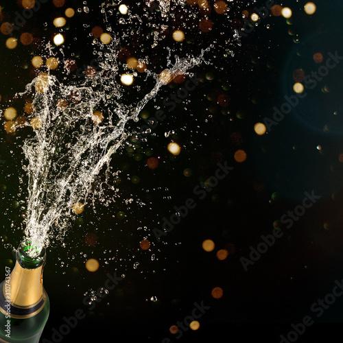 Obraz Bottle of champagne with splashing liquid, New year or other celebration theme. - fototapety do salonu