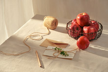 A Letter And Red Apples On Table.