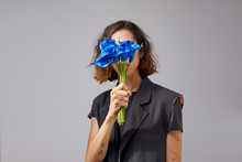 Portrait Of A Young Woman With Blue Flowers In Front Of A Grey Background
