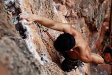 Muscular Climber Hanging On Rock