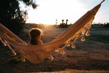 Little Girl In Hammock Watching Sunrise