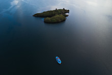 Aerial View Of A Small Island And A Blue Boat On The Sea