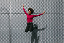 Happy Black Woman Jumping In T...