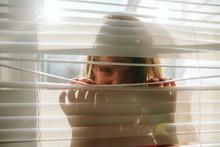 Child Peeks Through Window Slats