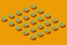 Pattern Of Fresh Kiwi Slices On Yellow Background