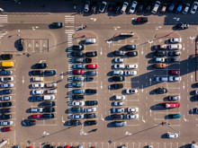 Aerial View From Drone Open Parking With Colorful Cars And Hard Shadows On A Gray Asphalt Background. Top View .