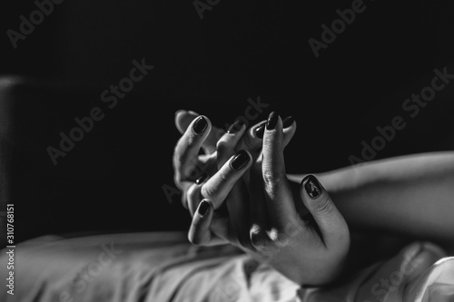 Close up on female young woman's girl's beautiful hands woman lying on the bed black and white nail polish in dark room crossed fingers on sheet gentle passion love temptation emotion concept