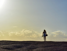 Silhouette Of Woman On Top Of A Mountain