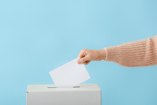 Voting Woman Near Ballot Box On Color Background
