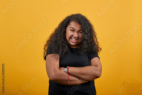 Fotomural Confused afro-american with overweight woman keeping hands crossed, squeezed teeth over isolated orange background wearing fashion black shirt