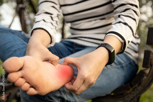 Fotografie, Tablou Plantar fasciitis,asian young woman holding her feet and massage with her hand s