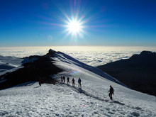 Hikers On The Ridge Ascend Mount Kilimanjaro The Tallest Peak In Africa.