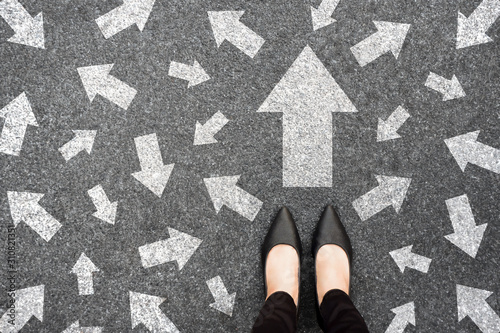 Obraz Feet and arrows on road background from above. Businesswoman standing on pathway with drawn white many direction arrows choice. Top view of A businesswoman black shoes. Motivation and growth concept. - fototapety do salonu
