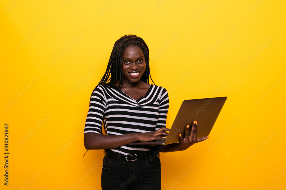 Fototapeta Young african positive woman using laptop and smiling isolated over yellow background