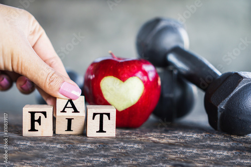 hand flipping fat to fit word with red apple and dumbbells ,healthy eating and s Fototapeta