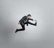 Time for movement. Man in office clothes running, jumping isolated on grey studio background. Businessman training in motion, action. Unusual look for sportsman, new activity. Sport, healthy lifestyle