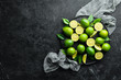Fresh green limes with leaves. Citrus fruits. On a black stone background. Top view. Free space for your text.