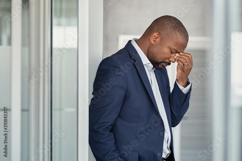Stressed businessman with headache standing