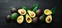 Fresh Avocado With Leaves On A Black Background. Top View. Free Space For Your Text.