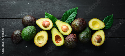 Fototapeta Fresh avocado with leaves on a black background. Top view. Free space for your text. obraz