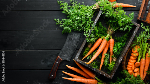 Fresh carrots on a black wooden background. Top view. Poster Mural XXL