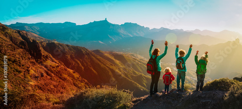 Obraz happy family travel in mountains at sunset, panorama - fototapety do salonu