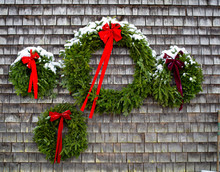 Four Wreaths Hang From A Shingle Wall Covered In Snow