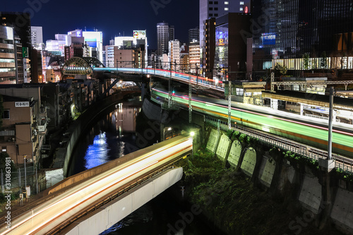 Photo Famous electronic Akihabara district by night with abstract blurry train