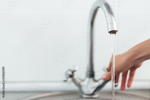 Foto woman hand opening silver faucet or water tap with metal washing sink in the kit