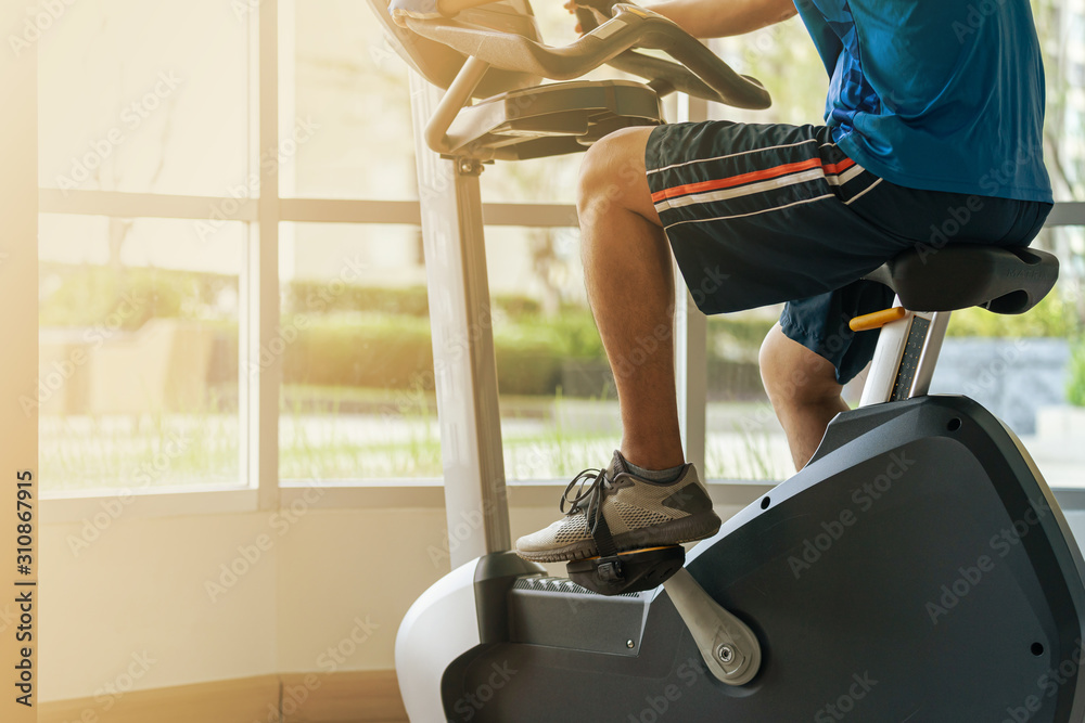 Fototapeta Close up of a man exercise in gym, Cycling on bike in fitness gym