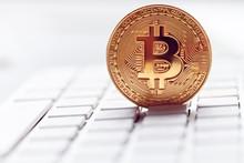 Gold Bitcoin In A Laptop Keybo...