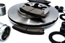 Automotive Spare Parts Of Disk Brake Pads, Disc Brake Caliper Piston, Disk Brake Repair KIt And Rotating Brake Disk On White Background.