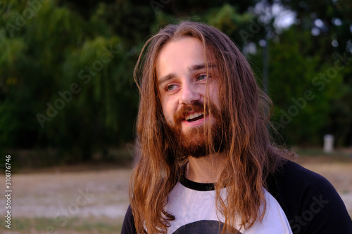 Handsome smiling young man with long hair posing at sand beach near forest Wallpaper Mural