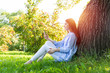 Young redhead woman using smartphone under tree