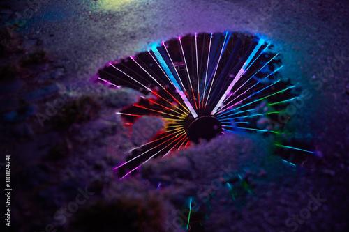 Obraz na płótnie Buntes Neonlicht als Reflexion im Wasser einer Pfütze