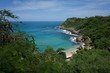 High angle shot from a cliff of the Puerto Escondido beach surrounded by forested hills