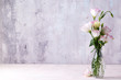 Leinwanddruck Bild Eustoma flowers in vase on table near stone wall, space for text. Blank for postcards