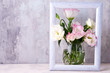 canvas print picture Eustoma flowers in vase in photo frame on table near stone wall, space for text. Blank for postcards