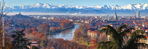 fototapeta na ścianę Aerial panoramic winter view on Turin city center with Mole Antonelliana, modern skyscrapers and other buildings, clear blue sky morning with Alps full of snow on background