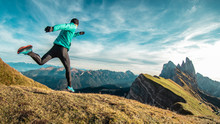 Young Man In Sport Trail Clothes Running On Seceda Mountain Peak At Sunrise. Puez Odle, Trentino, Dolomites, Italy.