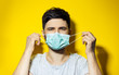 Studio portrait of young ill man, trying to put on, medical flu mask on yellow background.