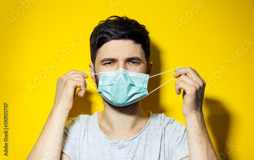 Studio portrait of young ill man, trying to put on, medical flu mask on yellow background Wallpaper Mural