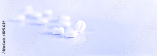 Fototapeta Medicine, pharmacy, pills. White pills on a light blue background. A scattering of tablets. Blurred background. Healthy lifestyle. Background for web site obraz na płótnie