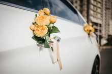 Wedding Decor On The Car Handle. Flower Decoration With Ribbons On A White Car