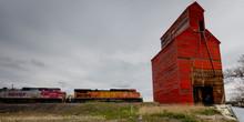 MAY 21,  2019, MONTANA, USA - Freight Train Drives By Red Grain Silo North Dakota