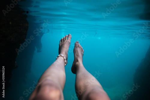Photo Underwater cave photo with woman's legs under surface, relaxing, swimming in tur