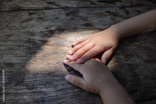 Fotografie, Obraz  The hands of two children are gently touching
